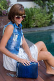 Young stylish woman in trendy outfit with snakeskin python luxury bag in hands. Woman with handbag near the swimming Royalty Free Stock Photography