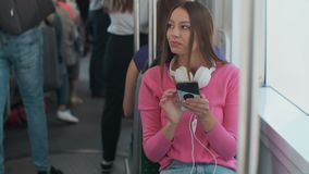 Young stylish woman using public transport, sitting with phone and headphones in the modern tram. Young stylish woman using public transport, sitting with phone stock footage