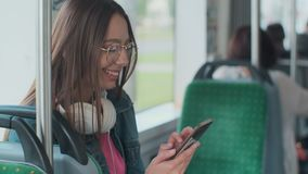 Young stylish woman using public transport, sitting with phone and headphones in the modern tram. Young stylish woman using public transport, sitting with phone stock video