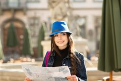 Young stylish woman walking on the old town street, travel with backpack and blue hat. Ukraine, Lviv stock photos