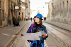 Young stylish woman walking on the old town street, travel with backpack and blue hat. Ukraine, Lviv stock image