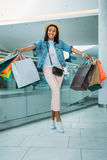 Young stylish woman walking with shopping bags, boutique shopping concept Stock Photo
