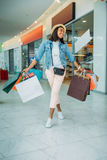 Young stylish woman walking with shopping bags, boutique shopping concept Stock Photography