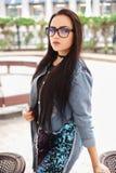 Young stylish woman wearing black eyeglasses and blue denim jacket royalty free stock photo