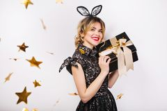 Young stylish woman on white background with gift box, celebrating, wearing black dress and black crown, happy carnival royalty free stock photography