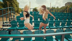 Beautiful girls at sunny day have fun and dancing at grandstand in slow motion stock video