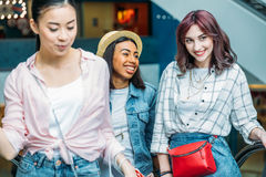 Young stylish women walking together in shopping mall, young girls shopping concept Royalty Free Stock Photo