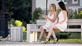 Young stylish women in white posing happily on bench at street and browsing smartphone together. Two trendy women with phone spending time together on bench stock video