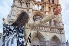 Young happy woman standing in front of the famous Notre Dame cathedral in Paris, hands raised up to the sky. Young stylishhappy woman tourist standing in front royalty free stock photos