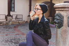 Young stylishly dressed woman in black knitted hat and glasses enjoying coffee from paper cup. Young stylishly dressed woman in black knitted hat and glasses Royalty Free Stock Image