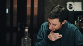 Young subtile man chewing eating food with friends at dining table. Young subtile caucasian brunette man in turtle neck sweater chewing eating food with friends stock video footage