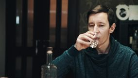 Young subtile man drinks vodka shot with friends at dining table. Young subtile caucasian brunette man in turtle neck sweater drinks vodka shot with friends at stock footage