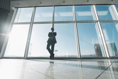 Young success business man standing satisfy against panoramic windows Royalty Free Stock Photography