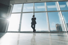 Young success business man standing satisfy against panoramic windows Stock Photos