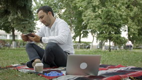 Young success businessman using tablet, laptop, mobile phone in the park stock video footage