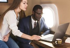 Young successful African-American businessman with glasses and an attractive female workmate blonde in a private jet stock images