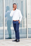 Young successful african businessman with mobilephone. Talking walking outdoor Royalty Free Stock Image