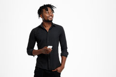 Young successful african businessman posing, holding phone over white background. Young successful african businessman in black shirt smiling, posing, holding Stock Photo