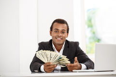 Young successful african businessman smiling, holding money, sitting at workplace. Royalty Free Stock Photography