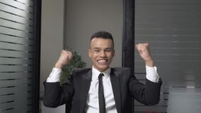 Young successful African businessman in a suit rejoices in victory, raised his fists upwards, sitting in the office. Laughing. 60 fps 4k stock video footage