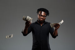 Young successful african businessman throwing money over dark background. royalty free stock images