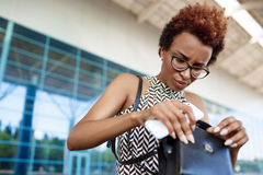 Young successful african businesswoman rummaging in bag over business centre. Royalty Free Stock Photo