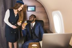 Young successful Afro-American businessman in glasses and a stewardess shows a bottle of wine in the cabin of a private royalty free stock photo