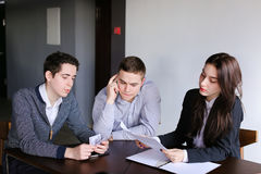 Young successful bankers two guys and girl check and agree docum Stock Images