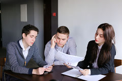 Young successful bankers two guys and girl check and agree docum Stock Image