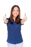 Young and successful. Beautiful young Asian woman looking at camera and showing her thumbs up while standing isolated on white Stock Images