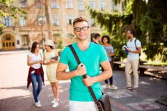 Young successful blond nerdy student is standing with bag and sm. Iles, behind are his classmates, park near campus, sunny day, carefree and enjoyable mood Royalty Free Stock Images