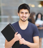 Young successful business with a folder smiling and looking at the picture Stock Photo