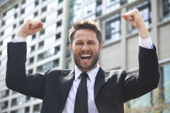 Young Successful Business Man Celebrating in City. A young successful man, male executive businessman arms raised celebrating cheering shouting in front of a royalty free stock images