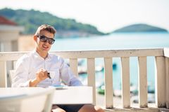 Young successful business man enjoying espresso coffee beverage in sunny marine panoramic cafe. Handsome entrepreneur drinking coffee on a luxury exotic seaside Royalty Free Stock Image