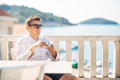 Young successful business man enjoying espresso coffee beverage in sunny marine panoramic cafe. Handsome entrepreneur drinking coffee on a luxury exotic seaside Stock Photo