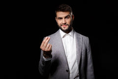 Young successful businessman asking for money over black background. Royalty Free Stock Images