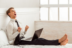 Young successful businessman. Attractive young blond businessman in white classical shirt and dark tie showing fists, screaming with happiness and using laptop Stock Photo