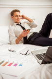 Young successful businessman. Attractive young blond businessman in white classical shirt and dark tie smiling, listening to music and resting while lying on bed Royalty Free Stock Photography