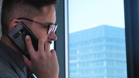 Young successful businessman with a beard makes a call on a smartphone on a window background with a view of downtown. High business building. Office in loft stock footage