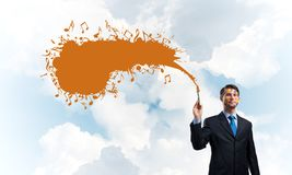 Business inspiration of young man. Young and successful businessman in black suit holding paintbrush in hand and smiling while standing with orange liquid splash Stock Photo