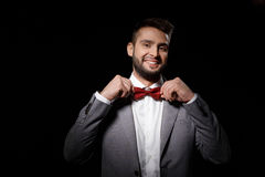 Young successful businessman correcting butterfly smiling over black background. Stock Image