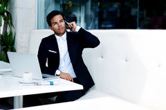 Young successful businessman in elegant suit talk on his mobile phone while sitting in modern luxury coffee shop Stock Photos