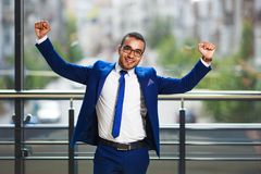 Young successful businessman expressing positivity while standin. G at the office building near window stock photo