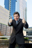 Young successful businessman happy and excited giving thumbs up okay sign Stock Photos