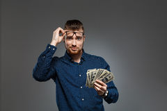 Young successful businessman holding money over dark background. Copy space. Royalty Free Stock Image
