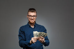 Young successful businessman holding money over dark background. Copy space. Royalty Free Stock Photos