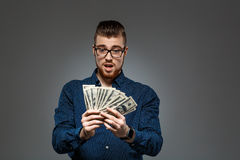 Young successful businessman holding money over dark background. Copy space. Stock Images