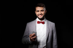 Young successful businessman holding phone smiling over black background. Stock Photos