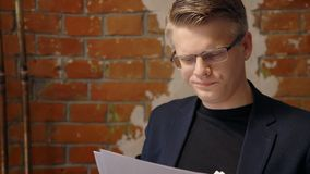 Young successful businessman is looking at project, standing in vintage interior. stock video