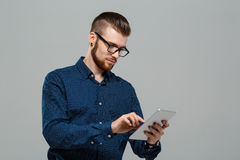 Young successful businessman looking at tablet over grey background. Young successful businessman in glasses looking at tablet over grey background. Copy space royalty free stock image